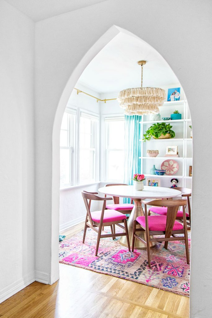 color full dining room after makeover with white walls, white cellular shades, bright pink chairs, tassel chandelier and colorful accessories