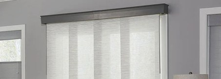 closeup of sliding panel shades over sliding glass door with decorative cornice covering track