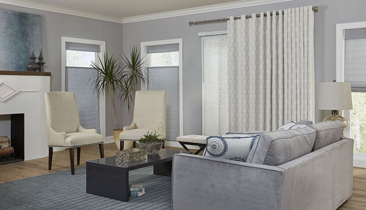 contemporary living room with grey walls, top down woven wood shades and sliding glass door with panel track blinds and white curtains on top.