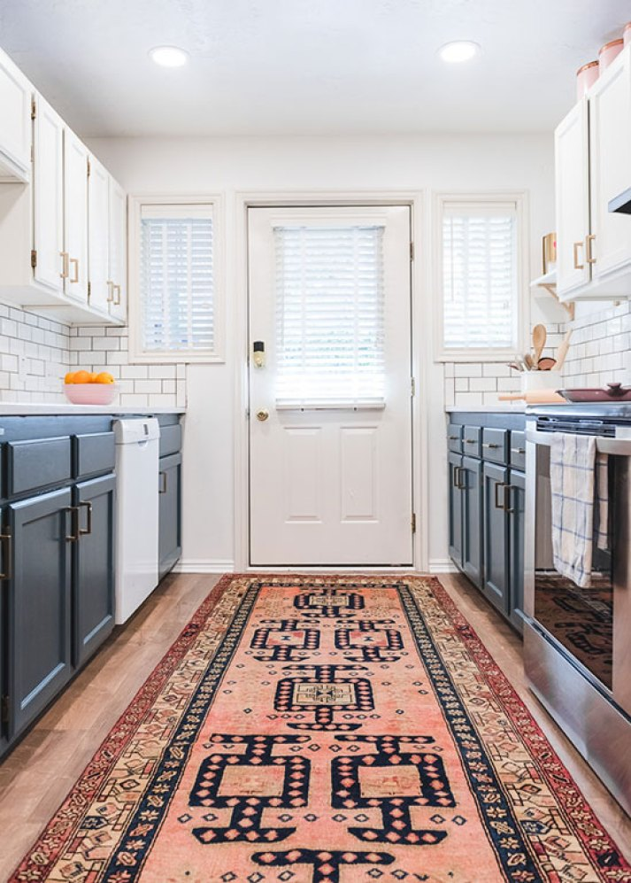bright kitchen with ping patterned runner rug, blue and white painted cabinets and white blinds on two small windows and back door with window