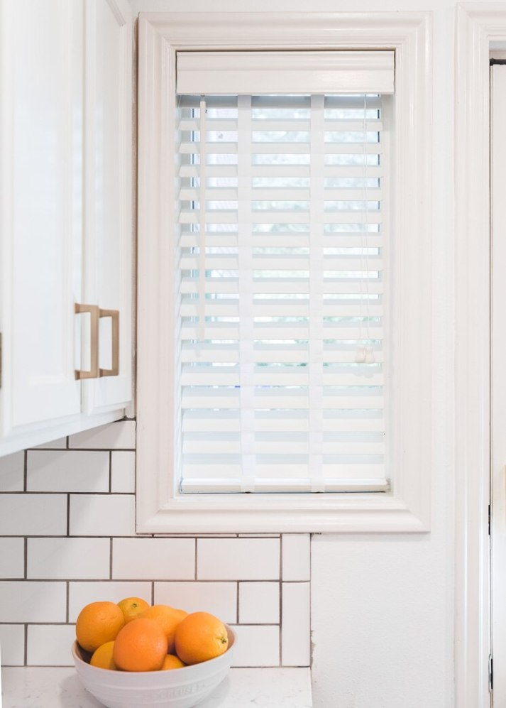 closeup of kitchen wall with subway tile and small window with white wood blinds with cloth tapes