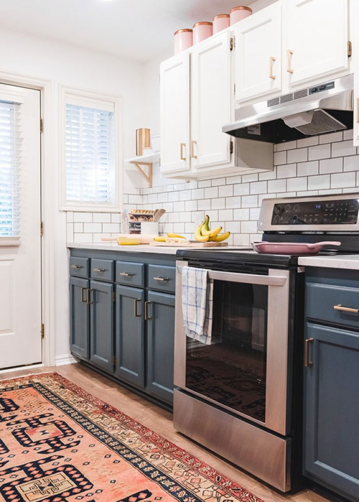 kitchen with blue lower cabinets, white upper cabinets, subway tile backsplash, white blinds and oriental runner rug