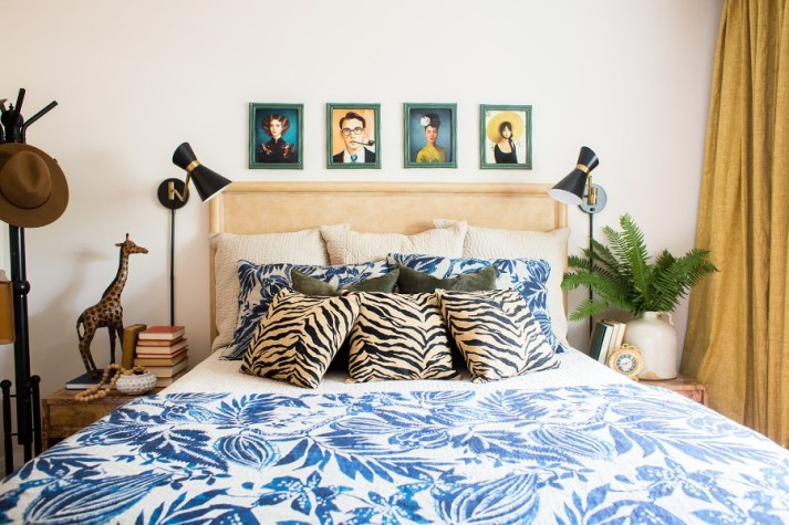 bedroom with blue floral comforter, animal print throw pillows, vintage paintings over bed and black mid century sconces over nightstands