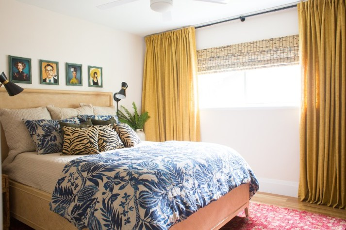 eclectic retro-inspired guest bedroom with woven wood shades on wide window and yellow curtains