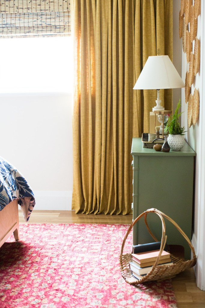 corner of bedroom with bamboo woven wood shades on window, yellow curtains, green dresser and basket of books on the floor