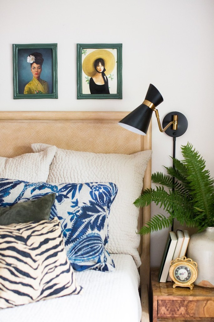 closeup shot of bed with linen headboard, mixed printed throw pillows, vintage portraits over bed and styled nightstand