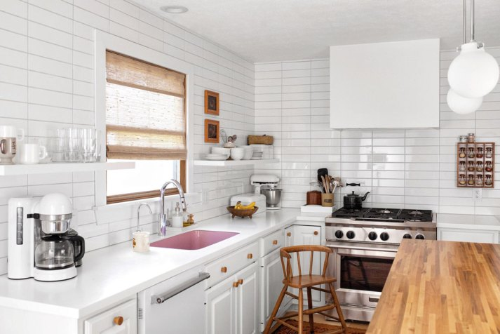 eclectic white kitchen with white quartz counters, white cabinets, stacked subway tile to the ceiling, woven bamboo window shade, open shelving and pink enamel sink