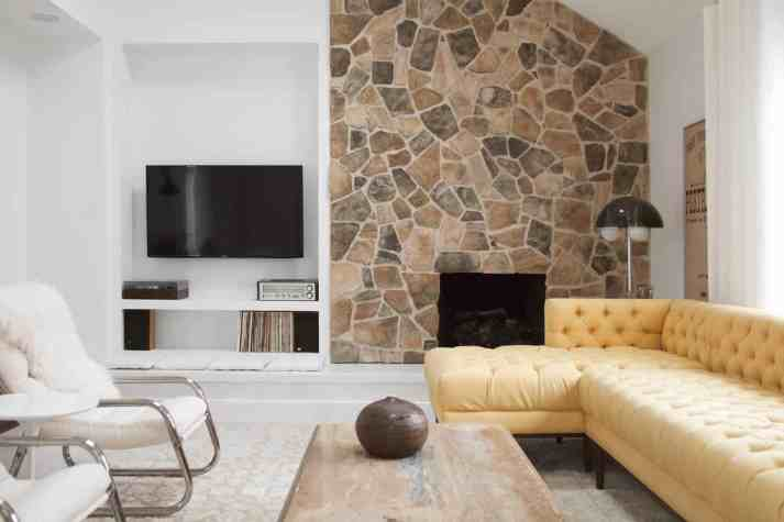 70s inspired living room with fieldstone fireplace, record player, chrome and white leather chairs, and tufted mustard sectional