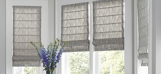 grey roman shades with wave print on bay window
