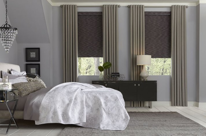 traditional bedroom with crystal light fixture over nightstand and windows covered with grey natural roller shades and taupe curtains