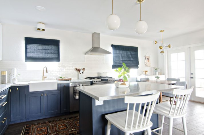 White and navy kitchen with mid century lighting and navy blue roman shades on windows.