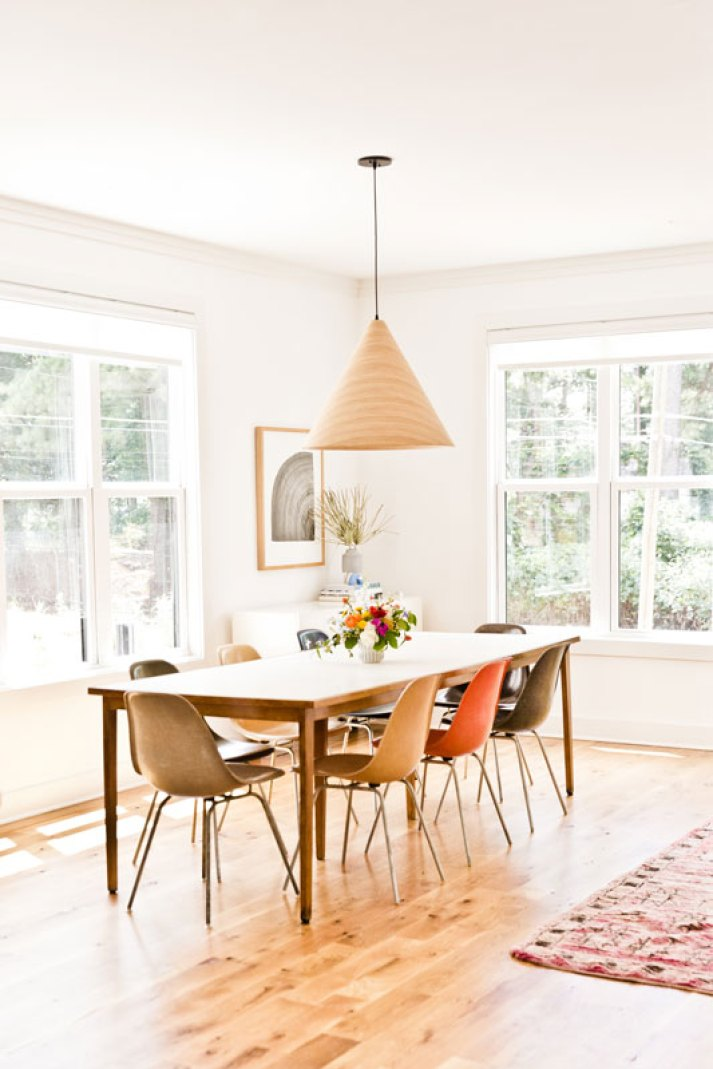 mid century dining room with molded herman miller chairs, wood cone light fixture and white roller shades