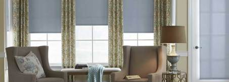 economy roller shades in semi opaque ice blue with easy rod pocket drapery in living room