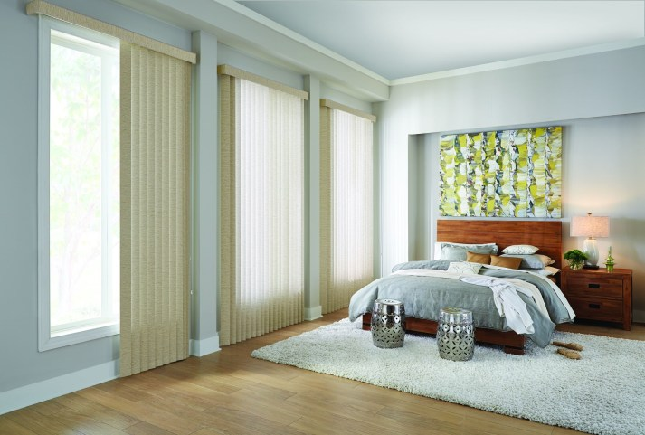 vertical blinds hang across wide windows in bedroom