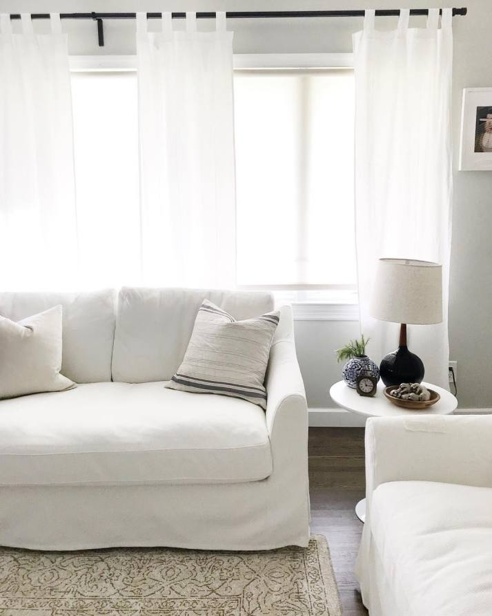 Neutral living room with white couches in front of wall of windows with white roller shades and white curtains.