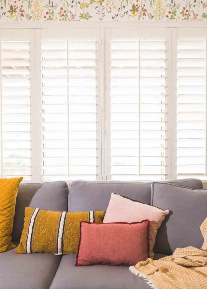 Grey fabric couch with pink and yellow pillows in front of large window with plantation shutters