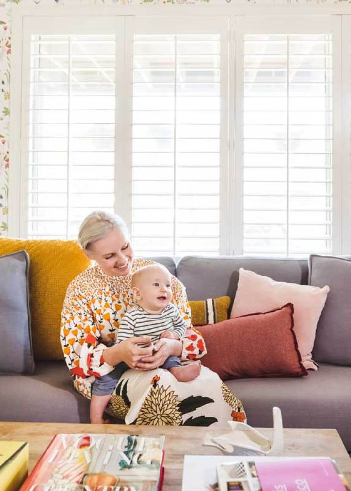 Woman holding baby boy in colorful living room in front of large window with white plantation shutters
