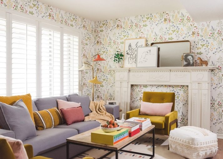 eclectic living room with floral wallpaper, yellow and orange accessories and large window with white shutters
