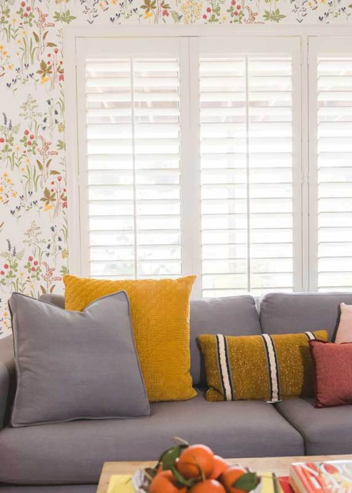 apartment living room with grey couch in front of white plantation shutters and floral wallpaper