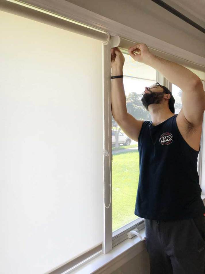 man installing white roller window blinds on wide window wall.