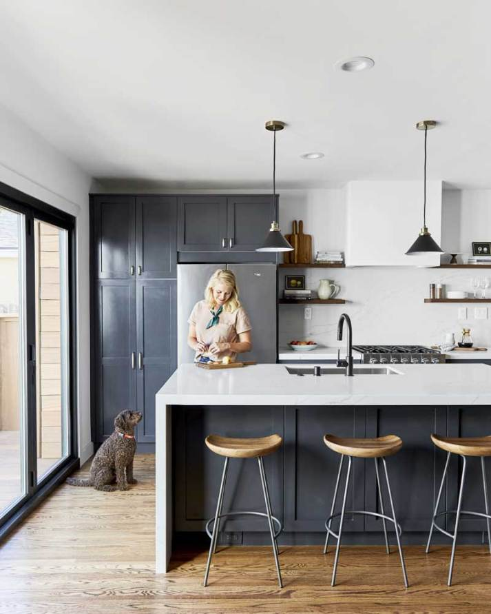 woman using cutting board in kitchen with dog sitting next to her.