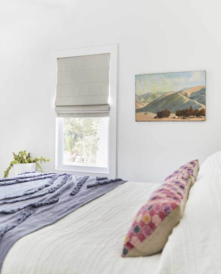 minimlaist bedroom with landscape hanging on wall and grey roman shade on window