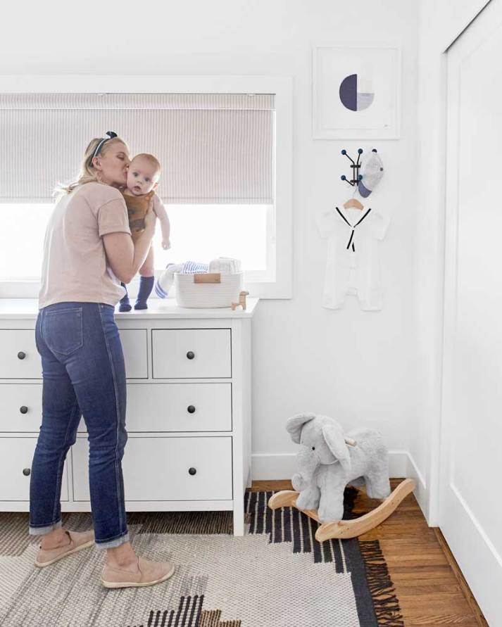 Ariel fulmer kissing baby in nursery with pinstripe roman shade over window