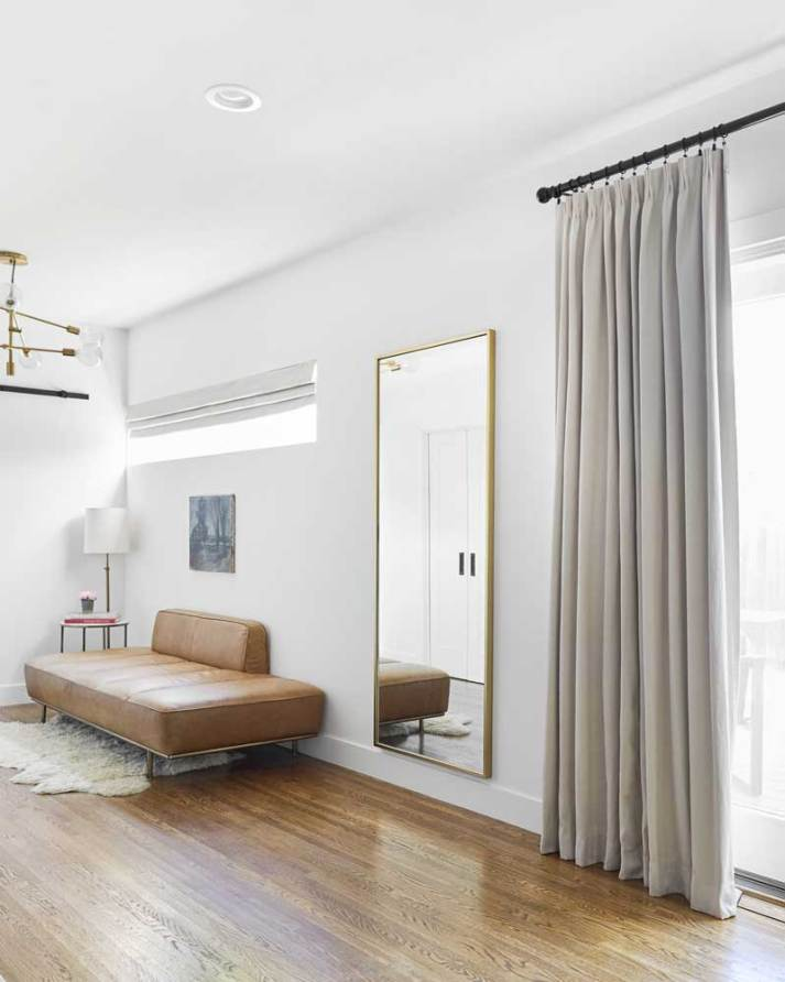 corner of room with long short window covered by grey roman shade and sliding glass door covered with blackout curtains in matching fabric.