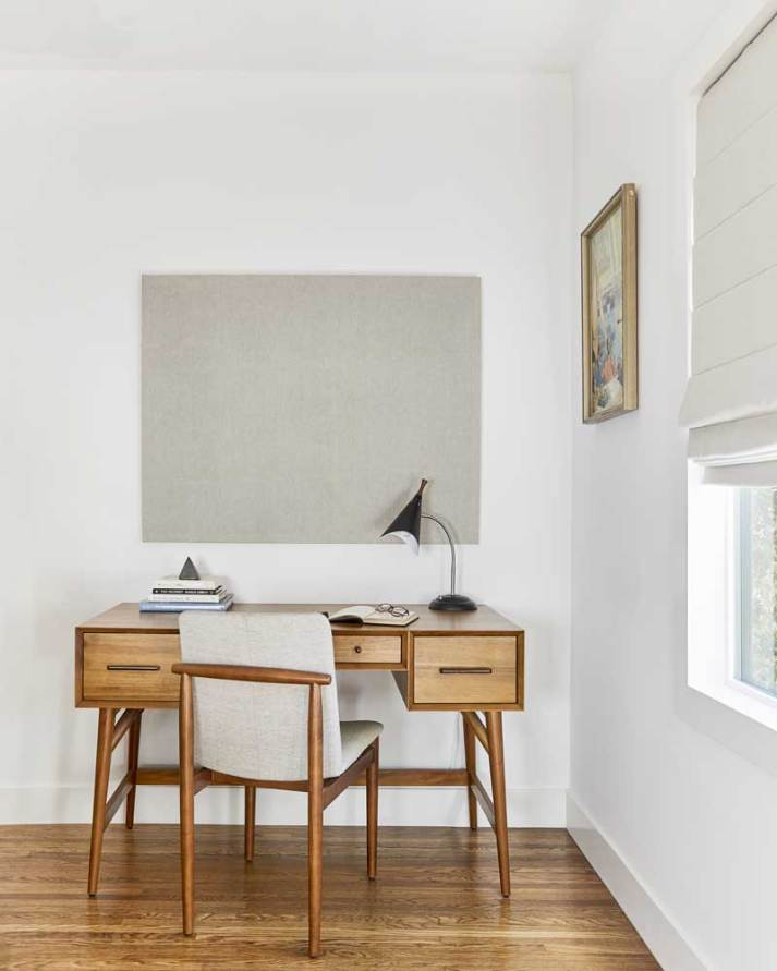 Mid century desk facing wall next to window covered with beige linen roman shade