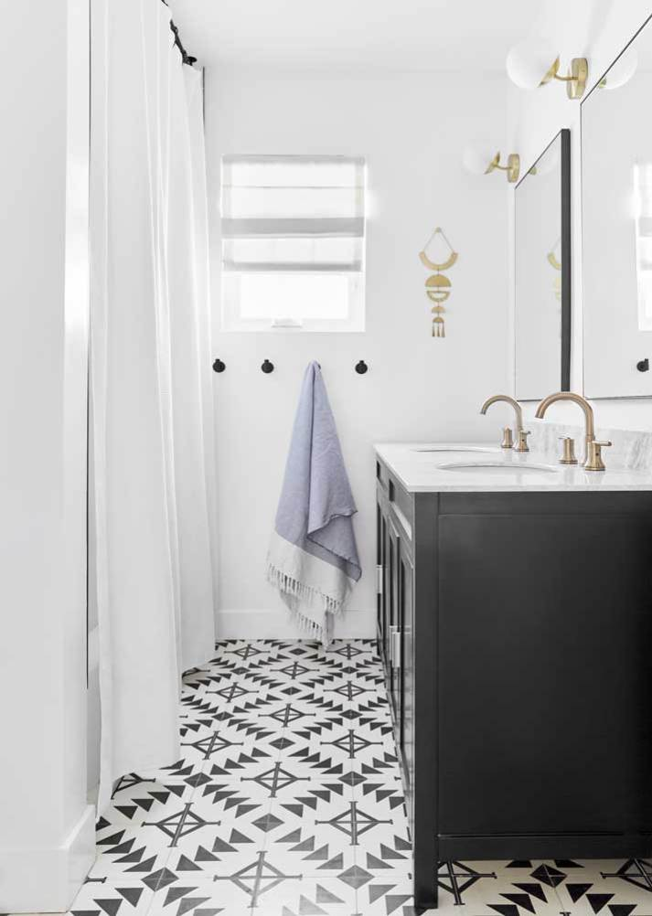 stylish small bathroom with patterned aztec tile, black vanity with white marble top and window at end with air white roman shade