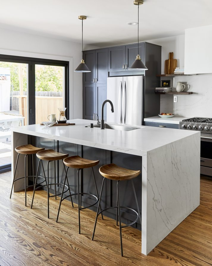 modern kitchen with dark navy cabinets, marble counters and black metal fixtures.