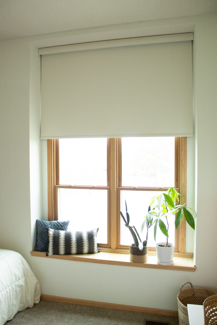 window seat with large white motorized roller shade in blackout fabric