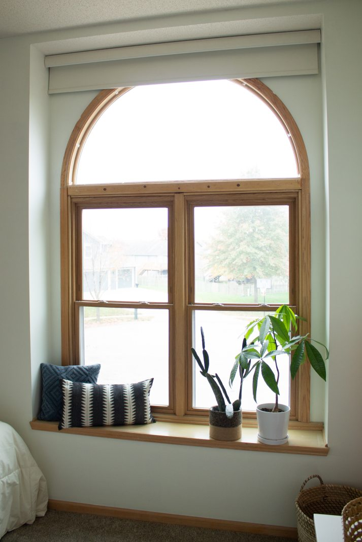 arched window over double windows covered with one large roller shade mounted inside window seat.