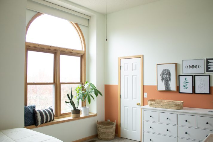 corner of bedroom with large arched window with wood frame and modern roller shade mounted in window inset.