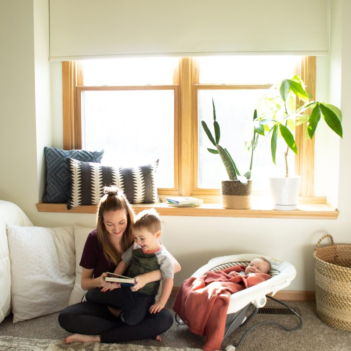 mom reading book to toddler and infant in eclectic nursery under window with roller shade