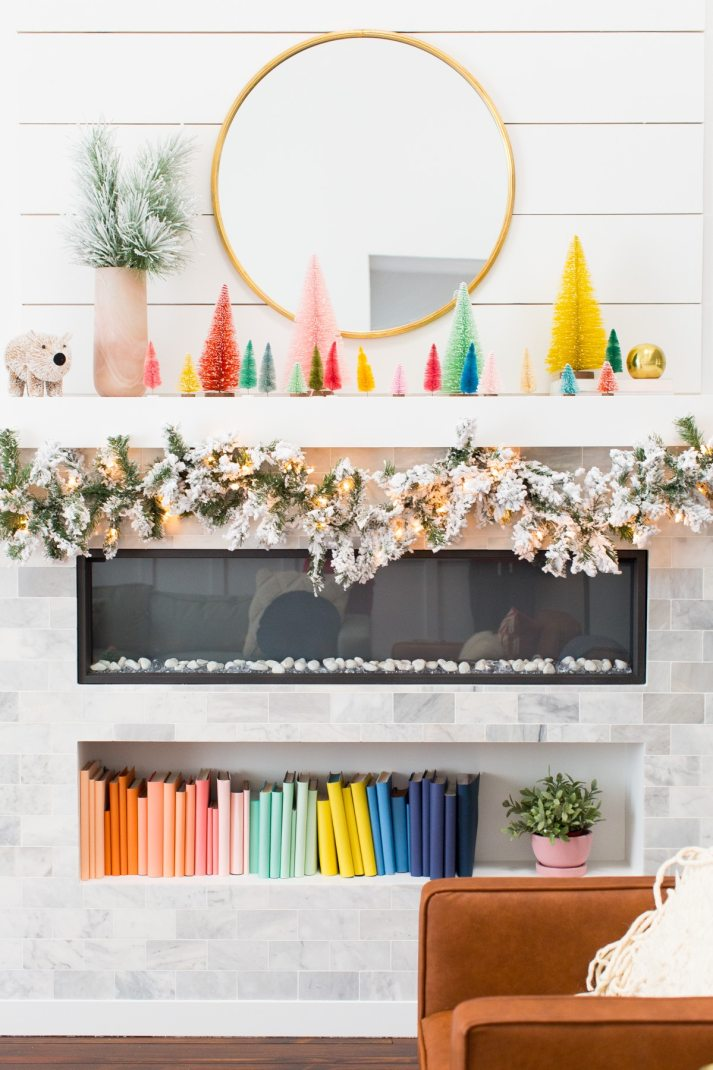 modern fireplace decorated for christmas with flocked garland and brightly colored bottle brush trees