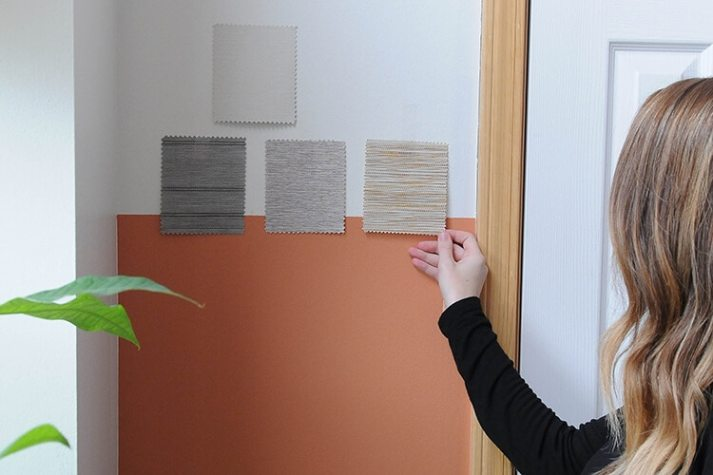 woman taping roller shade fabric samples up on wall to match to paint colors.