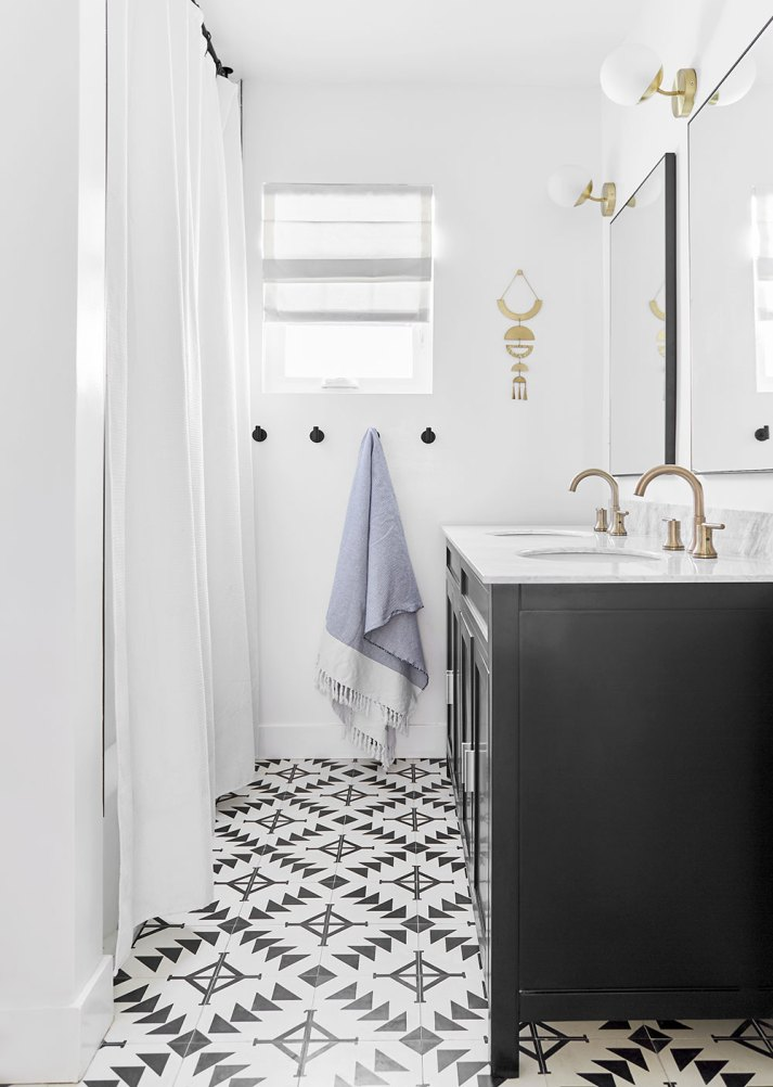 eclectic bathroom with black vanity, patterned tile and small window with white roman shade