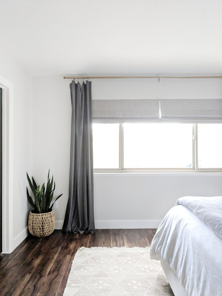 neutral bedoom with mother in law tongue plant in basket, bed with white and grey bedding and large window covered with taupe blackout shades and grey curtains
