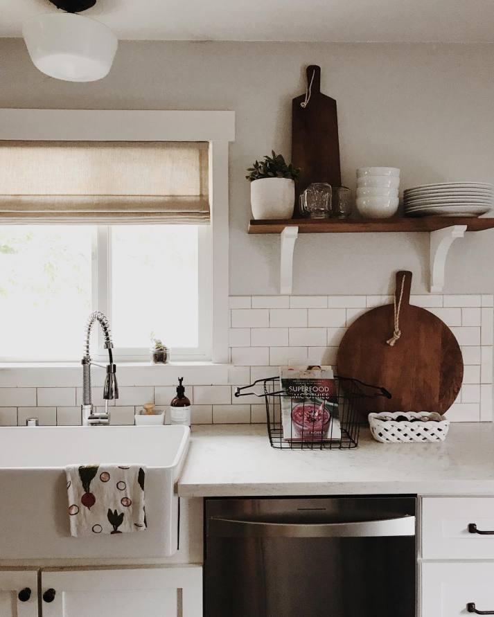 farmhouse kitchen with open shelving, farm sink and beige linen roman shade in window over sink