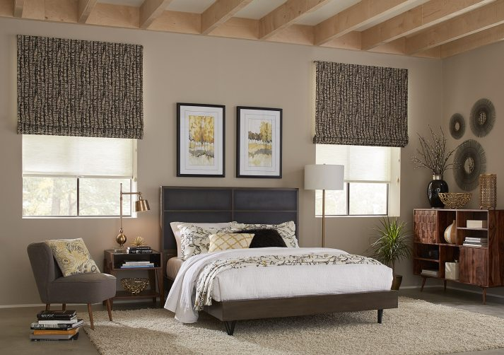 mid century inspired bedroom with two large windows covered with sheer white roller shades and brown roman shades with bark pattern