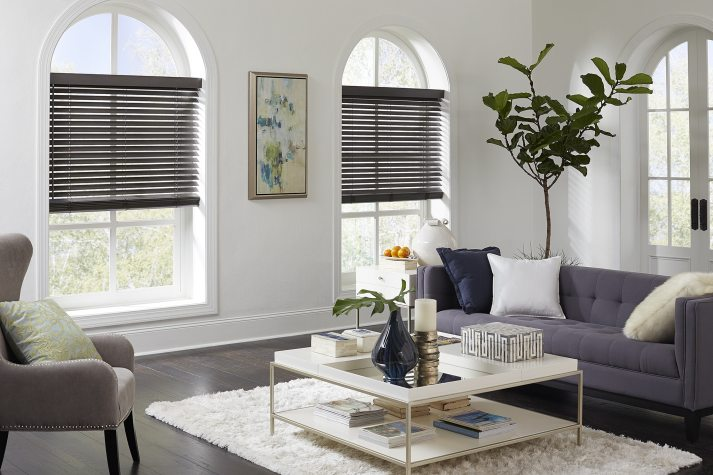 stylish living room with arched windows and dark wood blinds installed inside window opening.