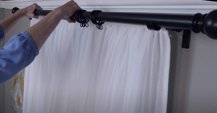 Woman hanging black metal curtain rod