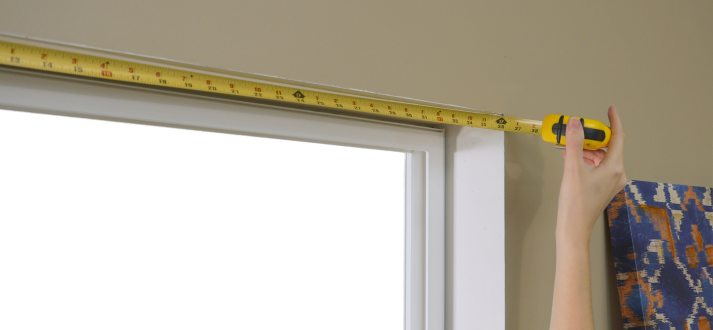 measuring top of window frame with tape measure