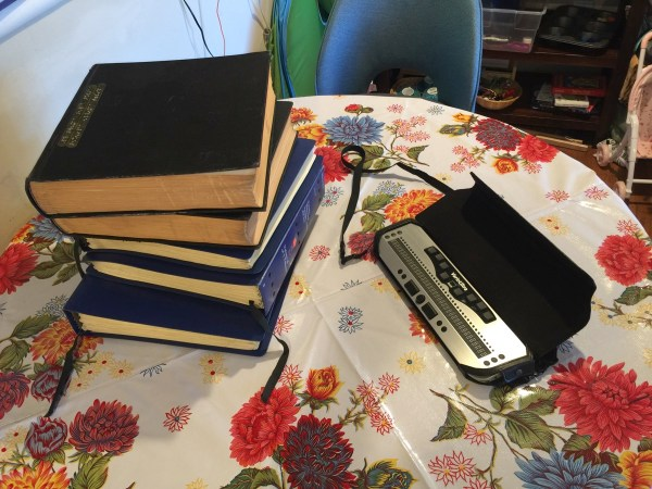 Photo of a stack of large Braille volumes, my library loan of Twenty Thousand Leagues Under the Sea, next to my sleek little VarioUltra.
