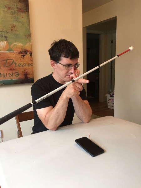A photo of Eric sitting at a table, balancing his white cane on one finger.