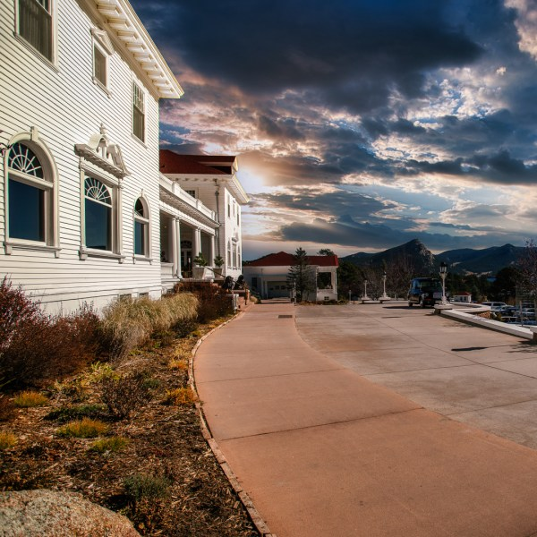 The sidewalk area outside of the Stanley Hotel. Puffy clouds in a blue sky and an image of the wide sidewalk in front of the main building.