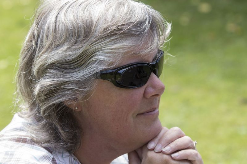 Head shot of Tracey with her chin resting on her folded hands. She is wearing a smile and dark glasses.