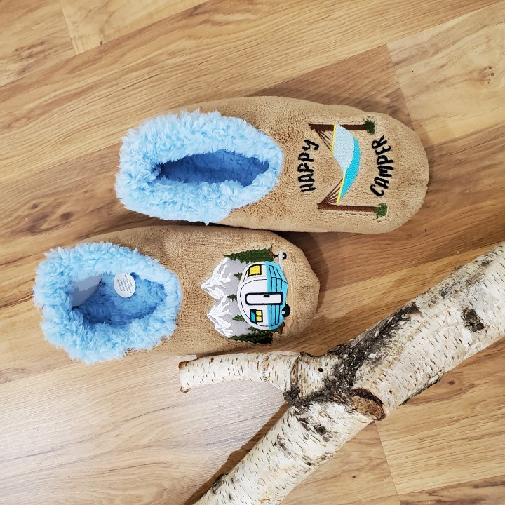 Suede-like Happy Camper slippers on wood-look floor next to birch log