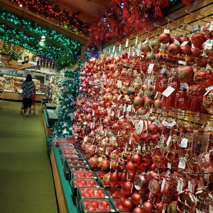 Traditional red and green glass  ornaments line the wall with red and green lighted evergreen garlands overhead for Christmas trends 2020.
